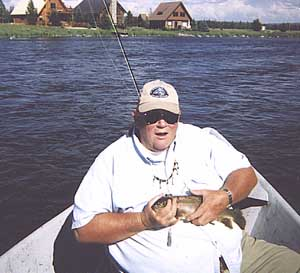 J.C. in drift boat holding brown trout on the Henry's Fork with houses on the bank.